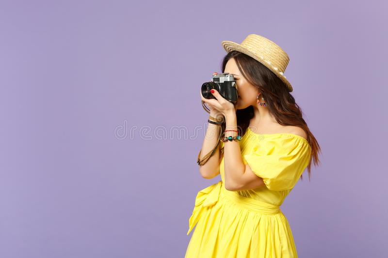 Side view of young woman in yellow dress, summer hat taking pictures on retro vintage photo camera isolated on pastel. Violet background. People sincere royalty free stock photo