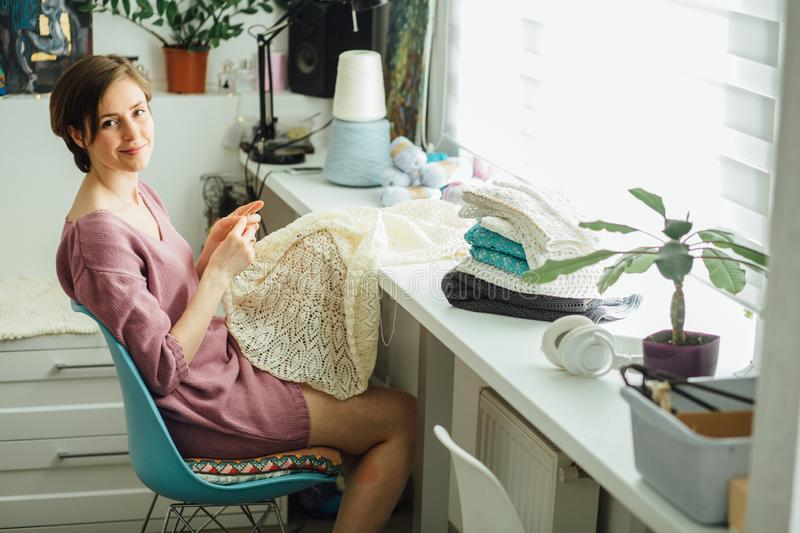 Side of woman designer knitting tender dress with crochet at studio home modern interior Female freelancer creative working at royalty free stock image