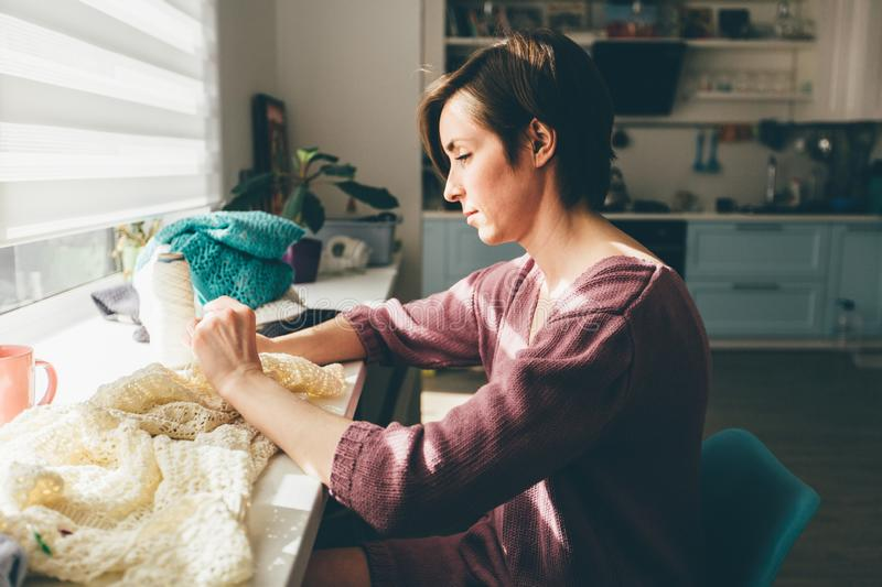 Side of woman knitting tender lace for tablecloth with crochet. Female freelancer creative working at cozy home workplace. stock images