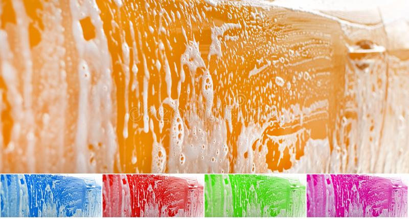 Side of yellow car washed, shampoo and foam on yellow surface. Color can be easily changed with hue shift in photo editor. Abstract car wash background royalty free stock images