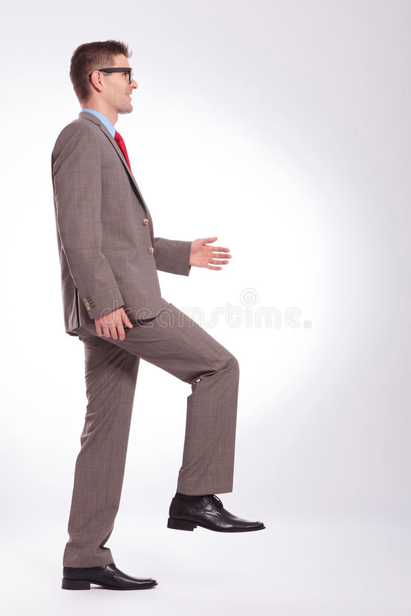 Side of a young business man walking forward royalty free stock images