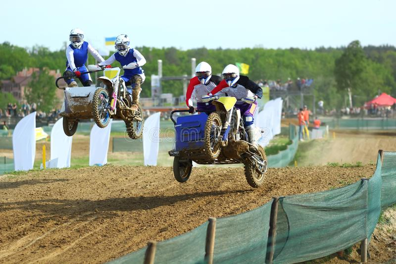 Sidecar motocross athletes overtaking in the air jump. On the dirt track royalty free stock photos