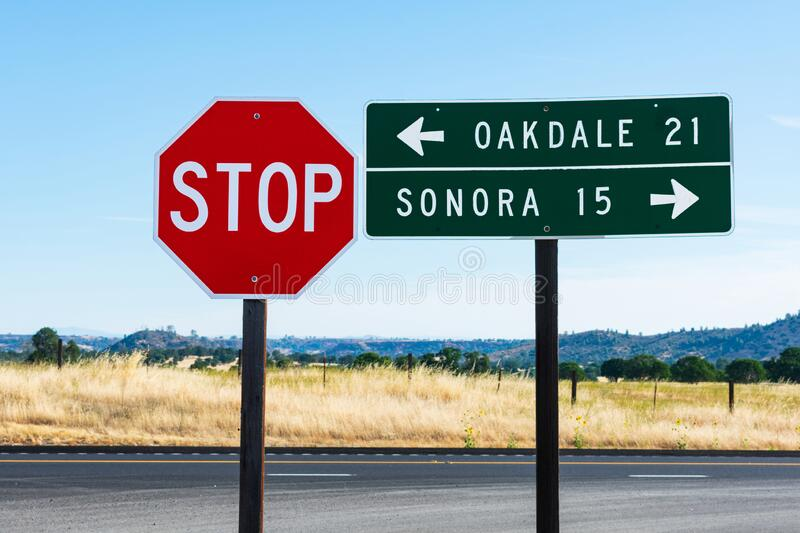An 8-sided red STOP sign and rectangular shaped green guide road sign with white lettering. Direction and distance to Oakdale and. Sonora. Background California stock images