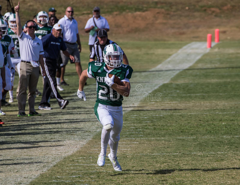Sideline Run. American football players in a game on Saturday afternoon in Redding, California. Shasta College (green) vs. Gavilan College royalty free stock images