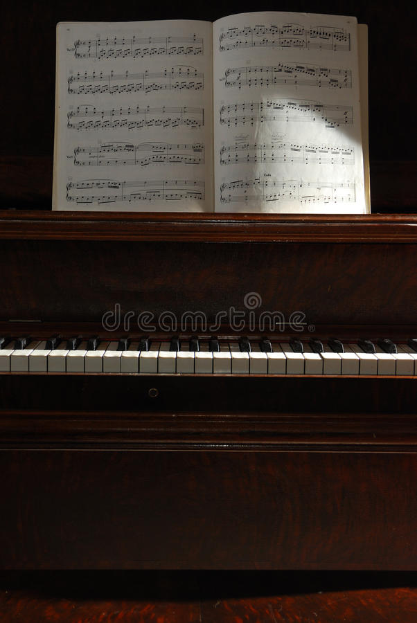Sidelit piano with music. stock images