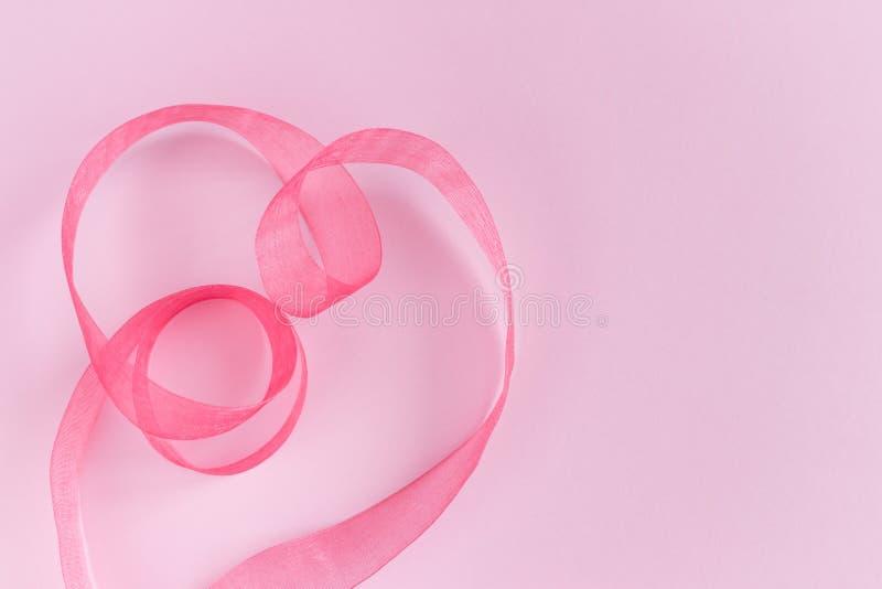 Siden- bandvågor för festlig rosa satäng i hjärtaform på rosa bakgrund arkivfoto