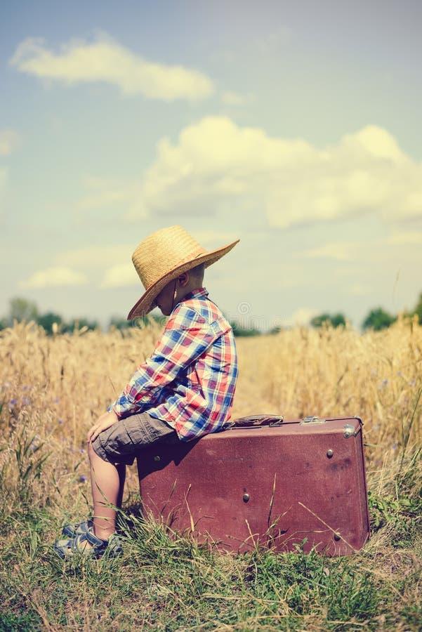 Sideview мальчика сидя на старом чемодане внутри стоковые изображения rf