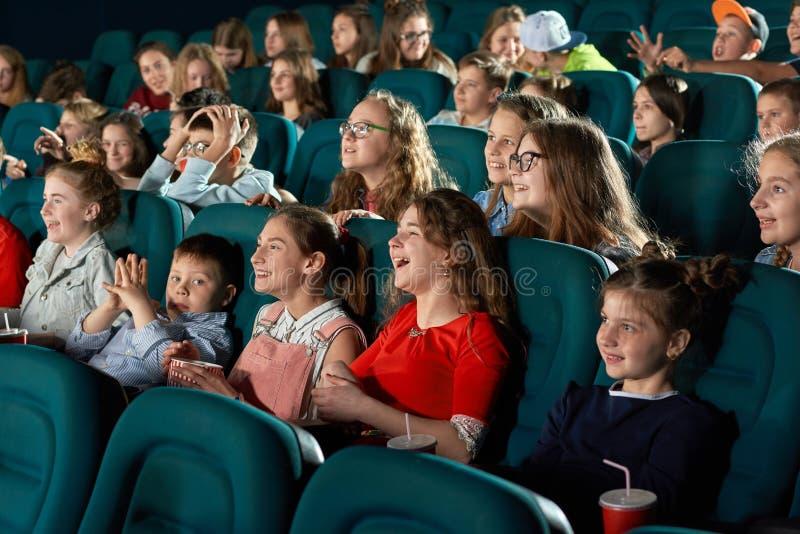Sideview av att skratta barn i bion royaltyfria bilder