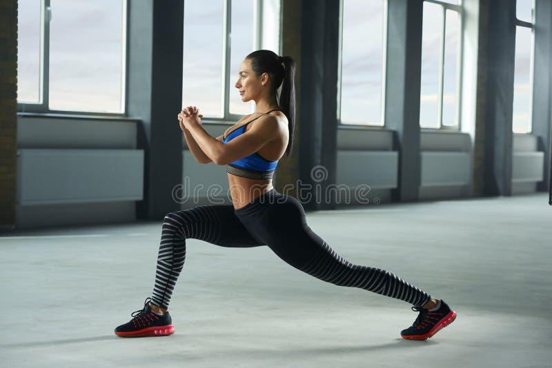 Sideview av den unga sportiga flickan med den idrotts- kroppen som gör nedfall i idrottshall royaltyfri bild