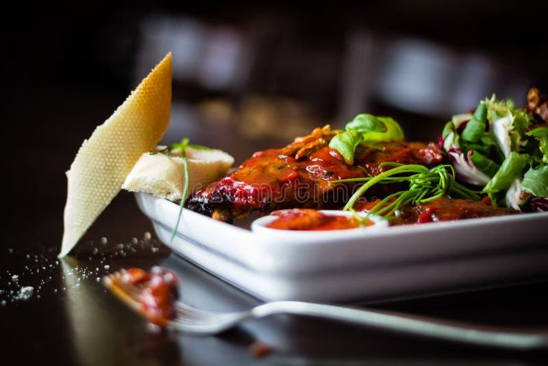 Sideview closeup av revbensspjäll med sallad, chilisås och bague fotografering för bildbyråer