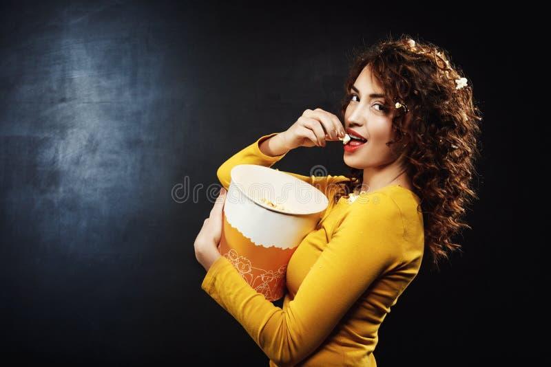 Sideview de jovem mulher surpreendente que come a pipoca no teatro de filme fotos de stock royalty free