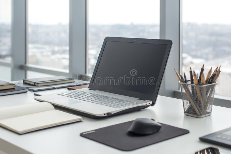 Sideview de la mesa de la oficina con el ordenador portátil en blanco y las diversas herramientas fotos de archivo