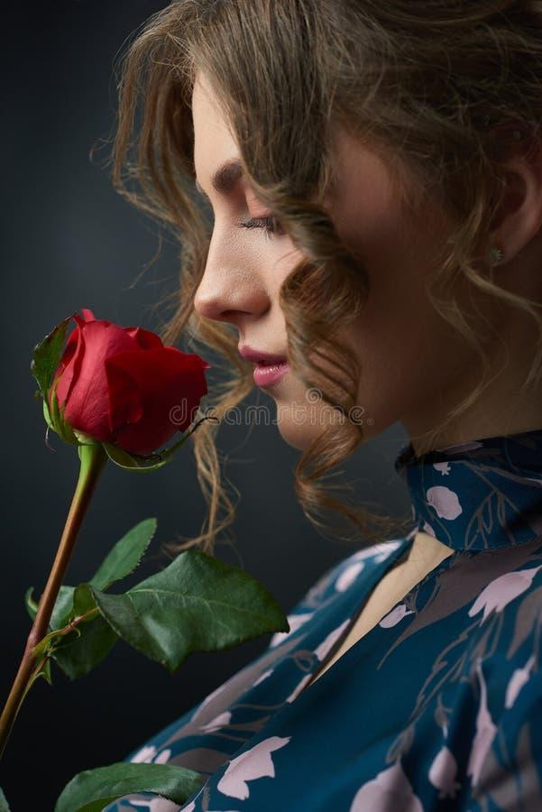 Sideview de una muchacha hermosa con la rosa del rojo imagen de archivo