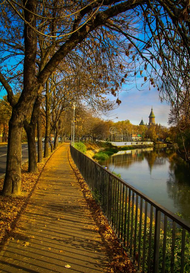 Sidewalk alongside Bega River and The Orthodox Cathedral in Timisoara. Autumn cityscape with sidewalk alongside Bega River and The Orthodox Cathedral in royalty free stock images