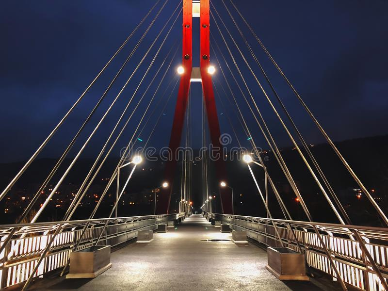 Sidewalk area going through a cable-stayed bridge with big steel cables, closeup at night time in bright lights stock photo