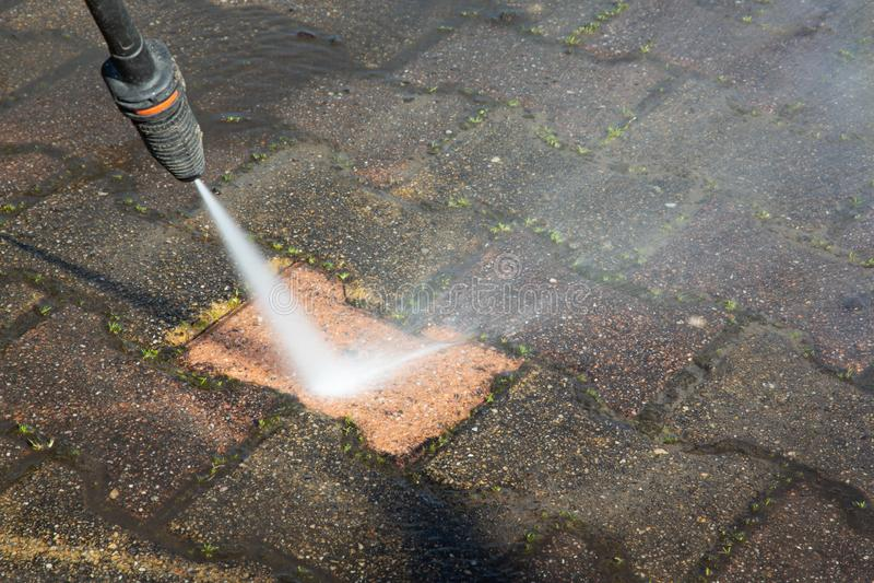 Sidewalk concrete block floor clean with high pressure water jet. A sidewalk concrete block floor clean with high pressure water jet stock images