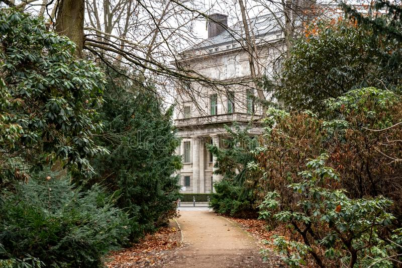 Sidewalk between conifer trees and evergreen bushes to retro building in Tiergarten park of Berlin Germany. Landscape with nobody. Tranquil landscape with nobody royalty free stock photo
