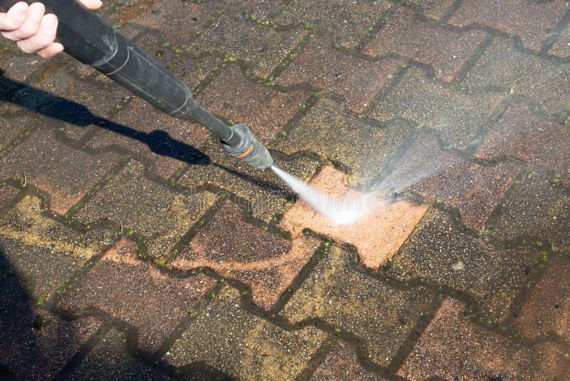 Sidewalk floor worker cleaning with high pressure water jet. A sidewalk floor worker cleaning with high pressure water jet stock photography