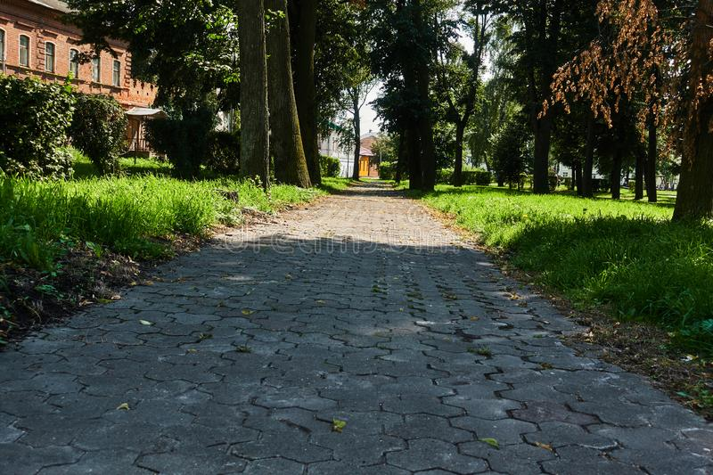 The sidewalk paved with brick blocks goes with the prospect of a distance. Comfortable straight the sidewalk.  stock photography