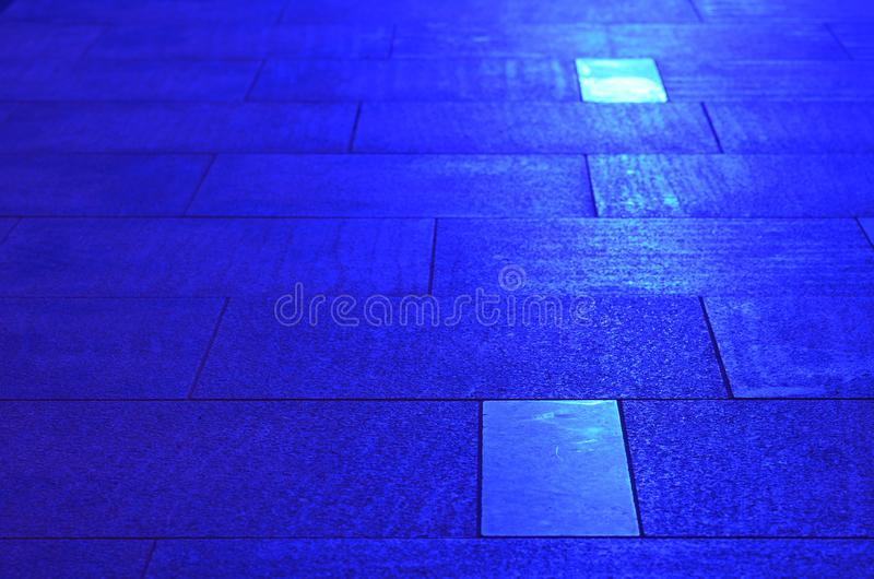 Sidewalk pavement slabs lit by blue light royalty free stock images