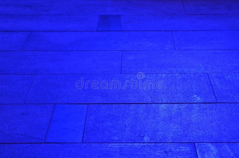 Sidewalk pavement slabs lit by blue light stock photography