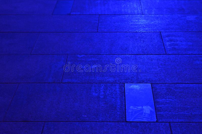 Sidewalk pavement slabs lit by blue light stock photos
