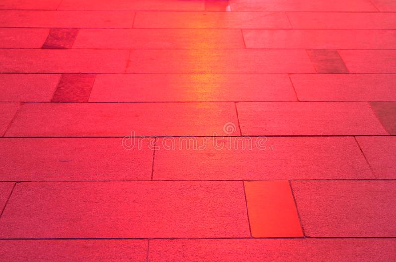 Sidewalk pavement slabs lit by red light royalty free stock image