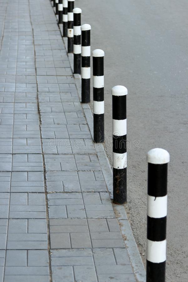 Sidewalk and road separated with safety bollards painted in black and white royalty free stock images