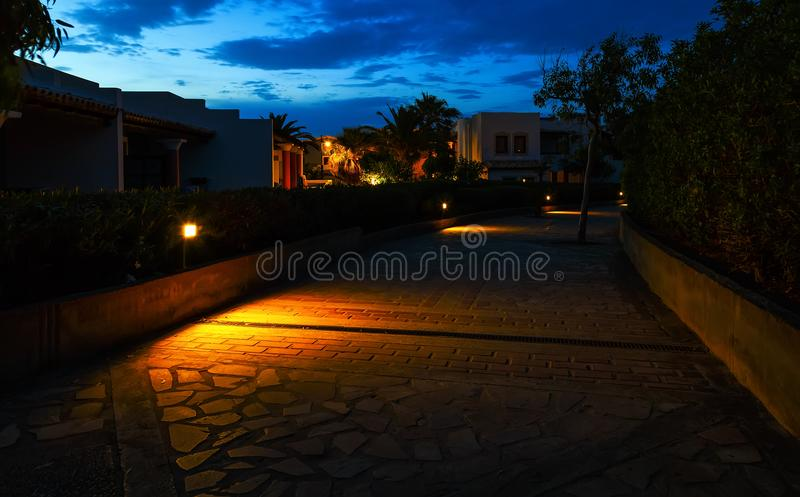 Sidewalk with stone masonry at night against the blue sky and clouds among the building of expensive hotels Greece Crete stock photos