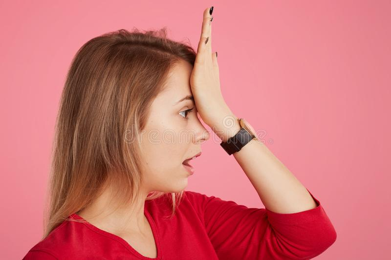 Sideways portrait of beautiful female keeps hand on forehead, remembers to do something important, demonstrates her bad memory, lo royalty free stock photo
