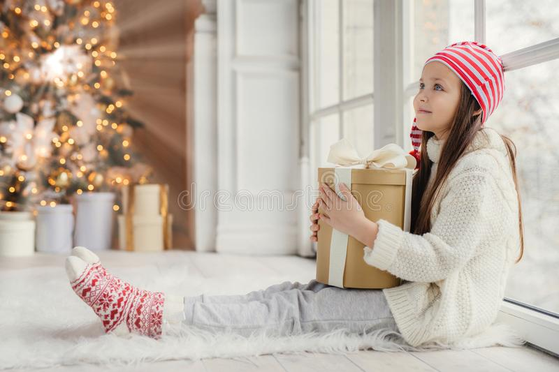 Sideways portrait of restful female child wears white sweater, trousers and warm socks, embraces wrapped gift, sits on floor in co. Zy room, admires New Year royalty free stock image
