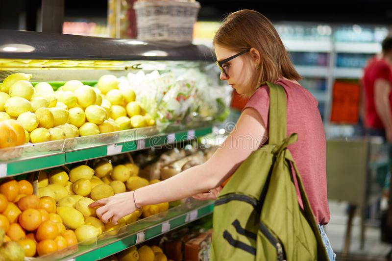 Sideways shot of beautiful young woman with bag, chooses fruits in grocer`s shop, touches to lemons, make purchases in supermarket stock photos