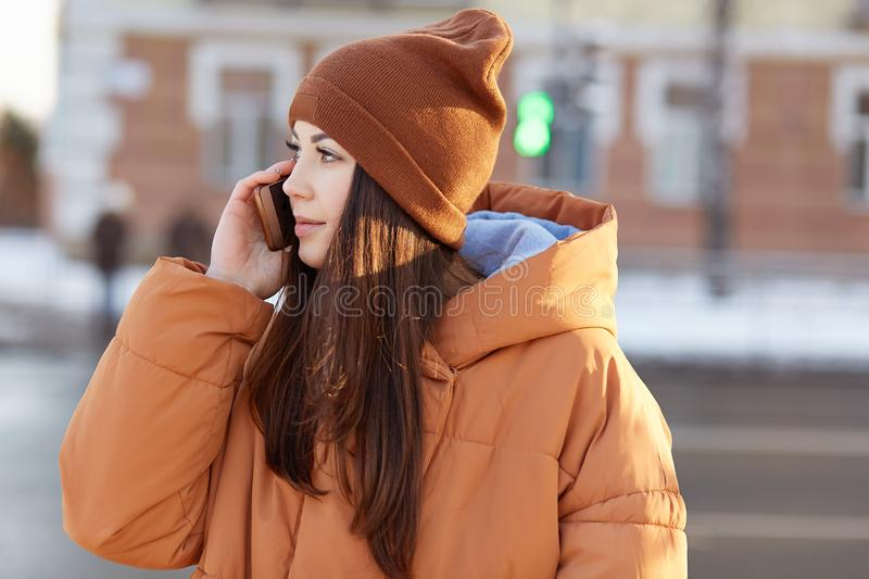 Sideways shot of brunette youngster with long hair, dressed in fashionable headgear and anorak, has telephone conversation outdoor royalty free stock photo