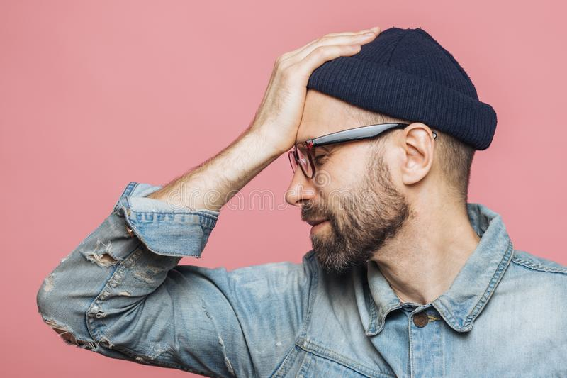 Sideways shot of displeased unhappy man with stubble keeps hand on forehead, closes eyes, feels desperately, wears stylish hat and stock photos