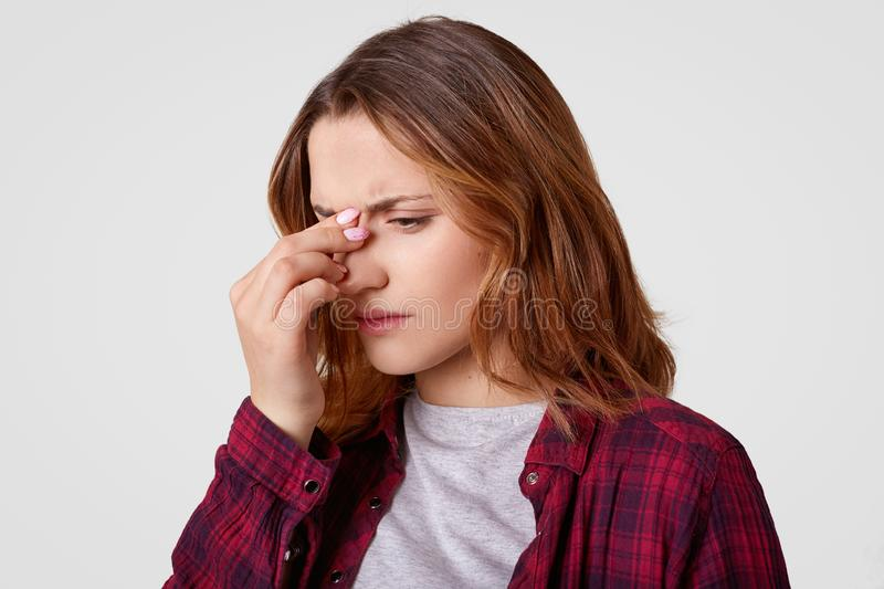 Sideways shot of dissatisfied woman concentrated down, keeps hand on nose, feels pain, finds out negative news, dressed in stock images