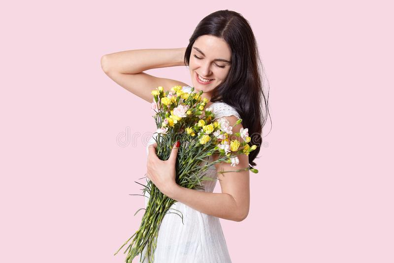 Sideways shot of pleasant looking young female model with dark hair, has gentle smile on face, recieves beautiful first spring royalty free stock photos