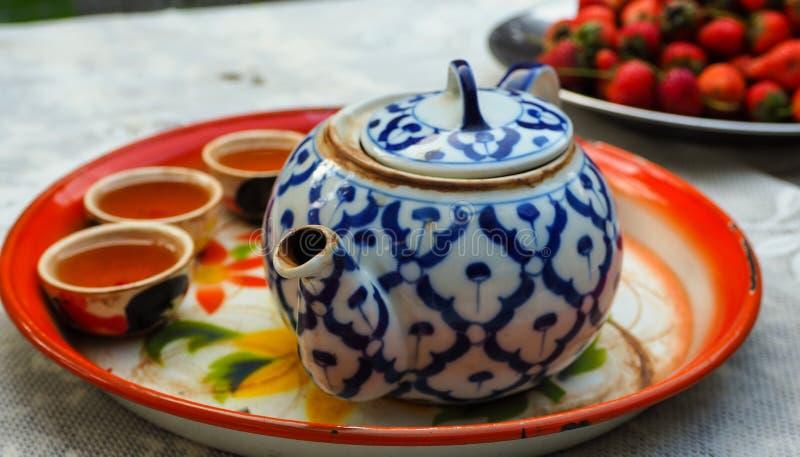 Sidewide kinesiskt te med torktumlaren och tekannan arkivfoton