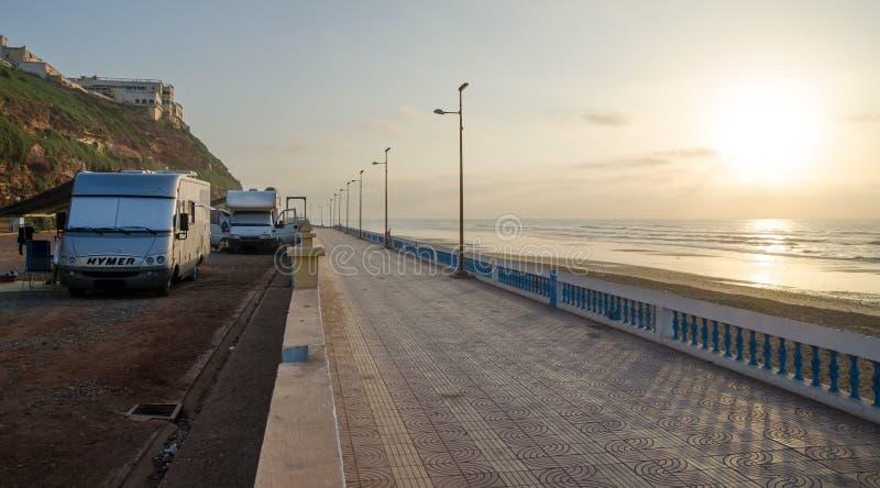 Sidi Ifni, Marrocos - 20 de setembro de 2013: Motorhomes no acampamento ao lado do passeio de pedra da praia durante o por do sol imagens de stock royalty free
