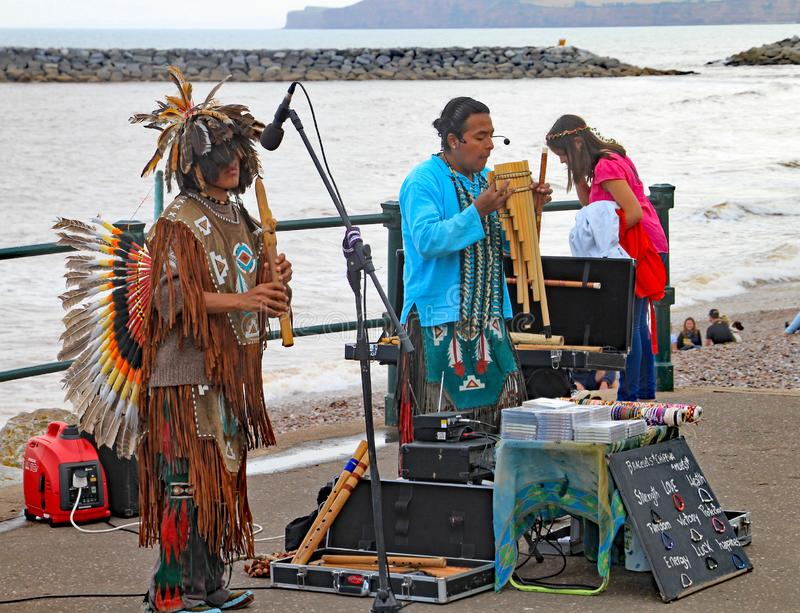 SIDMOUTH, ДЕВОН, АНГЛИЯ - 5-ОЕ АВГУСТА 2012: Перуанские музыканты улицы играя на эспланаде на неделе Sidmouth ежегодной фольклорн стоковое фото rf