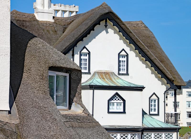 SIDMOUTH, DEVON - 1º DE ABRIL DE 2012: A residência cobrida com sapê velha bonita está na costa de Sidmouth em um dia ensolarado imagens de stock