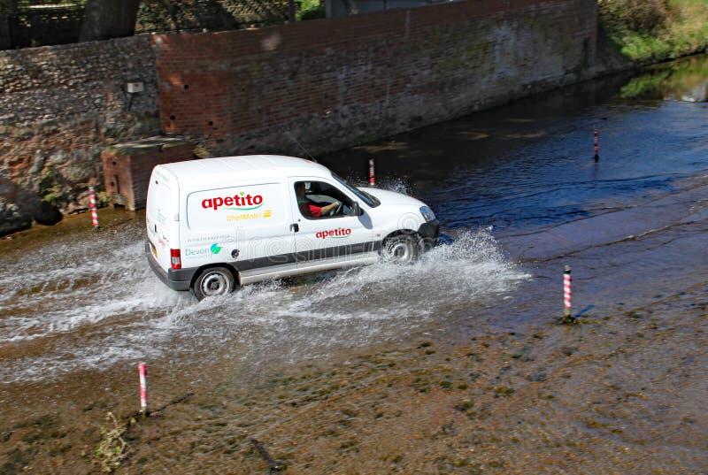 SIDMOUTH, DEVON - 1º DE ABRIL DE 2012: Uma camionete viaja com o baixio no rio Sid imagem de stock