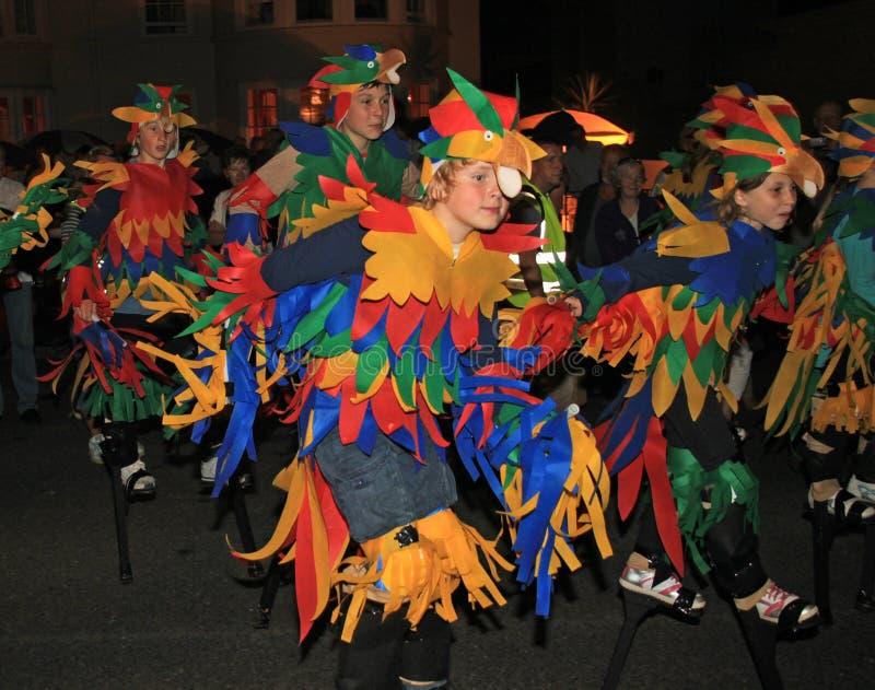 SIDMOUTH, DEVON ANGLIA, SIERPIEŃ, - 10TH 2012: Dzieci ubierali w górę gdy colourful odprowadzenie na stilts i papugi biorą udział zdjęcia stock