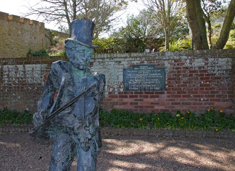 SIDMOUTH DEVON - APRIL 1ST 2012: Statyn av den Sidmouth fifflaren står i Connaught trädgårdar och firar minnet av 50 år av arkivfoton