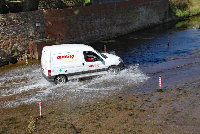 SIDMOUTH, DEVON - APRIL 1ST 2012: A van travels through the ford on the river Sid stock image