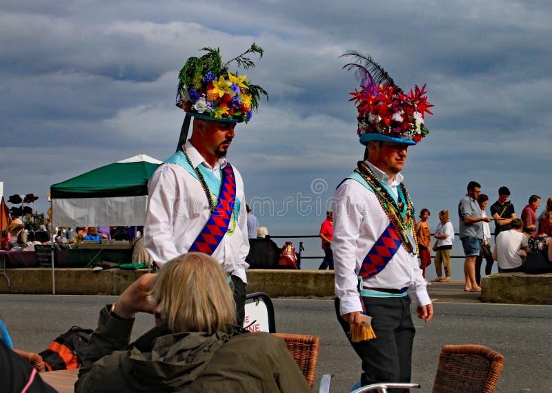 SIDMOUTH, DEVON, ENGELAND - AUGUSTUS ACHTSTE 2012: Twee Morris-dansers in extravagante hoofdtoestelgang langs de Promenade tijden royalty-vrije stock afbeeldingen