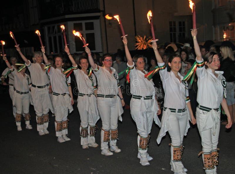 SIDMOUTH, DEVON, ENGELAND - AUGUSTUS TIENDE 2012: Een troup van jonge damemorris dansers houdt hoog hun vlammende toortsen aangez stock fotografie