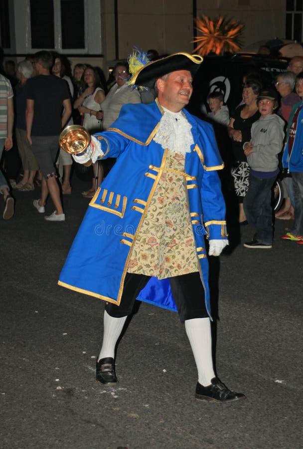 SIDMOUTH, DEVON, ENGELAND - AUGUSTUS TIENDE 2012: Stadscrier leidt de nacht sluitend optocht langs de Promenade E stock foto's