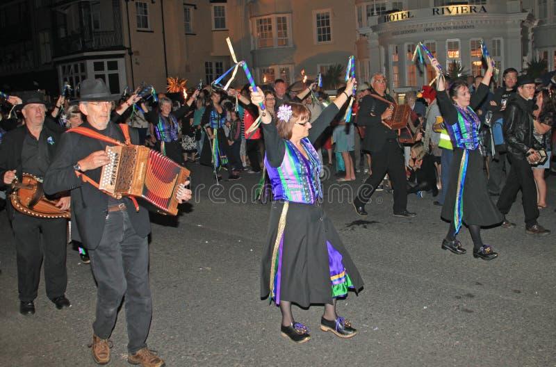 SIDMOUTH, DEVON, ENGLAND - 10. AUGUST 2012: Eine Gruppe Musiker und Klotztänzer gekleidet in der Malvenfarbe und im Grün und im H lizenzfreies stockfoto