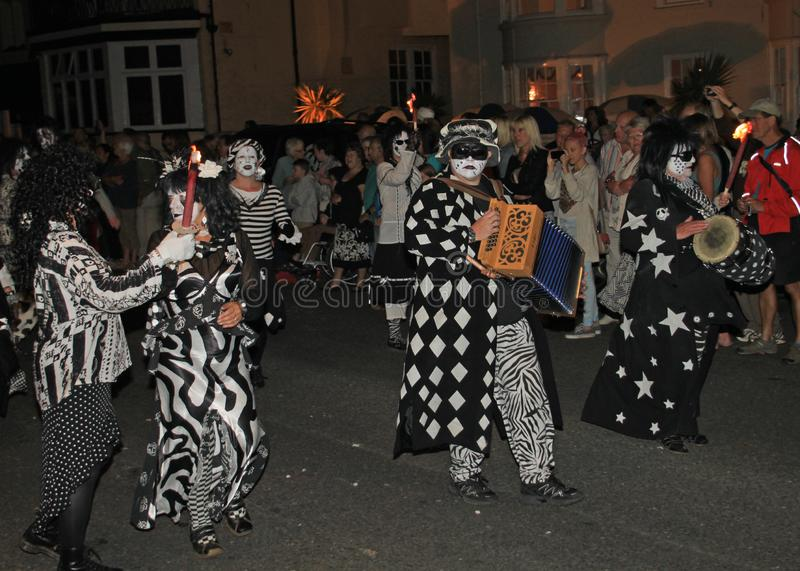 SIDMOUTH, DEVON, ENGLAND - AUGUST 10TH 2012: A dance troup dressed in very eerie black and white costumes take part in the night royalty free stock photography