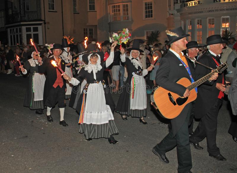 SIDMOUTH, DEVON, ENGLAND - AUGUST 10TH 2012: A group of Welsh performers takes part in the night time closing procession of folk stock image